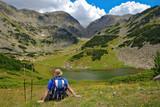 Hiker having a rest near lake at national park Pirin, Bulgaria poster