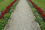 Gravel path surrounded by flowers poster