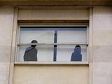Silhouettes masculine et féminine à la fenêtre dun bureau poster