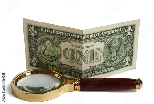 Photo of a magnifier and dollar on a white background