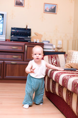 Little boy stand on hardwood floor in typical home interior