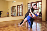 Two ballroom dancers practicing in their studio poster