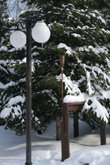 Street lamp with fir on a background covered by snow