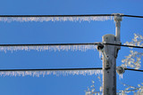 Icicles hanging from power lines after an ice storm poster