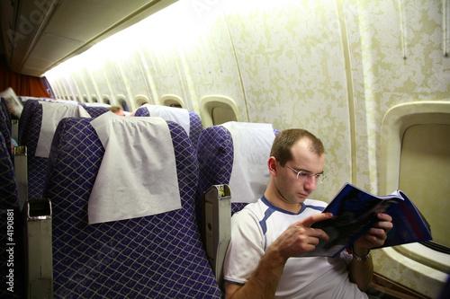 man read journal in an airplane
