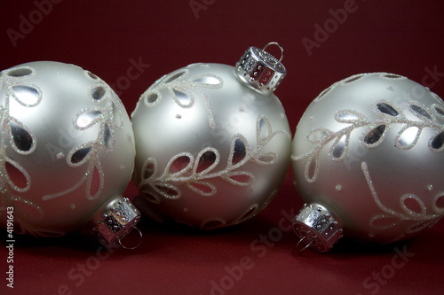 Silver Christmas Tree Ornaments on Red Background