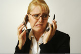 Business woman expresses stress as she shuffles two cell phones. poster