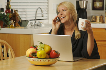 Woman in her kitchen on cell phone sitting in front of laptop.