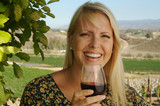 Beautiful woman smiling as she is wine tasting on a summer day. poster