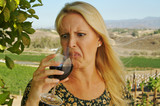 Beautiful woman cringes as she is wine tasting at a winery. poster