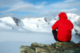 Climber sitting in front of big glaciers