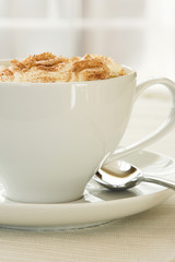A side view image of a cup of Cappuccino in a white cup.