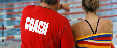 A coach, giving instruction to a young female swimmer