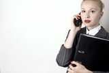 Businesswoman with black binder using a  phone poster