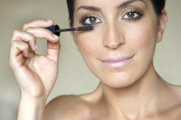 Mulher fazendo maquiagem nos olhos