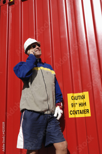 engineer against red freight container