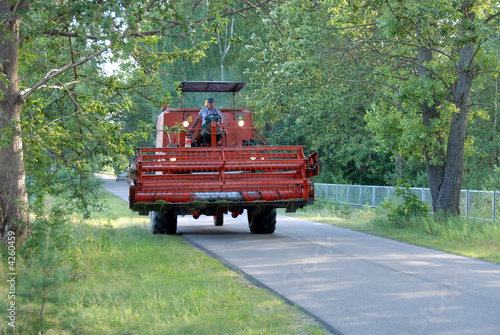 red combine harvester on the road somewhere in polish village