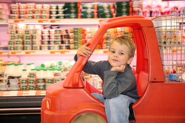 boy in the toy car - shoppig cart in the shop