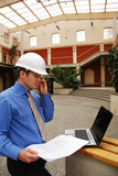 contractor in hardhat calling by phone and work with laptop poster