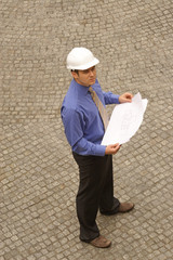Young architect standing on pavement with blueprints