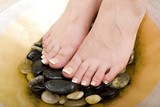 Pedicured feet on pebbles poster