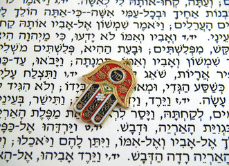 Red Hamsa kabala good luck charm on Hebrew bible