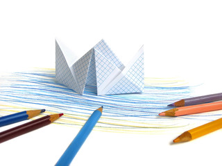 Paper ship on drawing sea background with multicolored pencilse