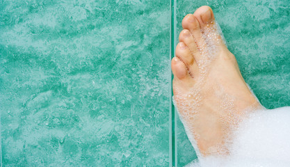 woman foot in foam bath room on tile
