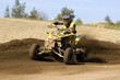 Teenager on a yellow quad bike sliding