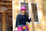 Smiling female construction worker with pink hardhat poster