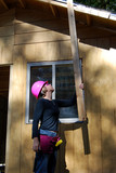 Female construction worker lifts wood poster