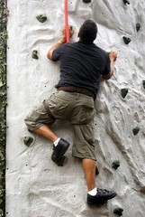young man climbing wall