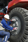 engineer fixing large truck tire poster
