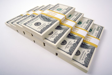 Stacks of Hundred Dollar Bills on a white background.