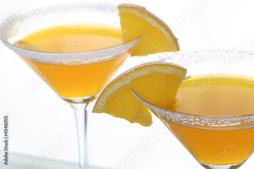 martini glass with orange cocktail and piece of citrus 7