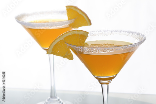 martini glass with orange cocktail and piece of citrus 8