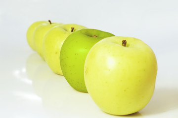 Group of yellow apples with a green one