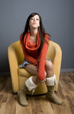 Full length view of teenage girl sitting in yellow armchair. poster