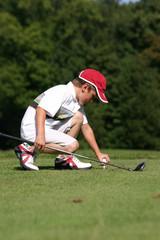 petit golfeur plante un tee