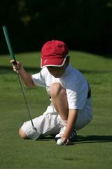 petit golfeur place sa balle