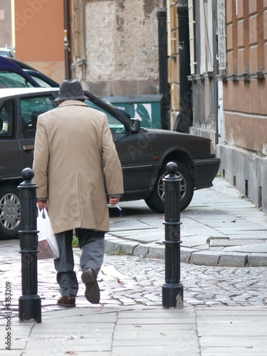 Elderly man walking along a street holding a bag and a cigarette