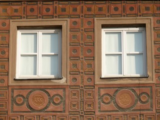 Close up of two white windows against decorated brown wall