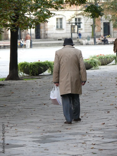 Elderly man walking along a street, holding bag and cigarette