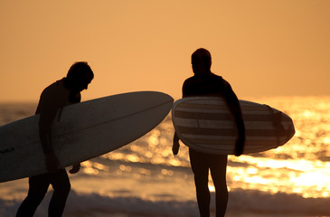 Two surfers at the beach at sunset