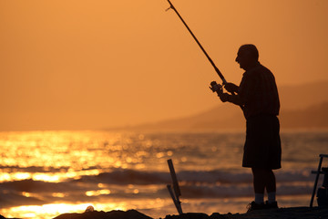 Man fishing at sunset in Malibu