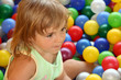 The little girl on a background of multi-coloured balls