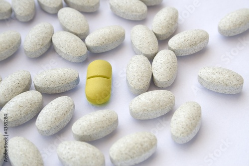 Yellow pill among gray tablets