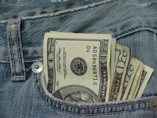 Pocket money, fan of american dollars in jeans pocket