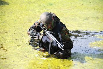 Soldat kämpft sich durch das Wasser