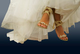Wedding shoes on barefooted legs of the bride poster